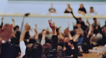 une assemblée dans un amphi où beaucoup de participants lèvent la main
